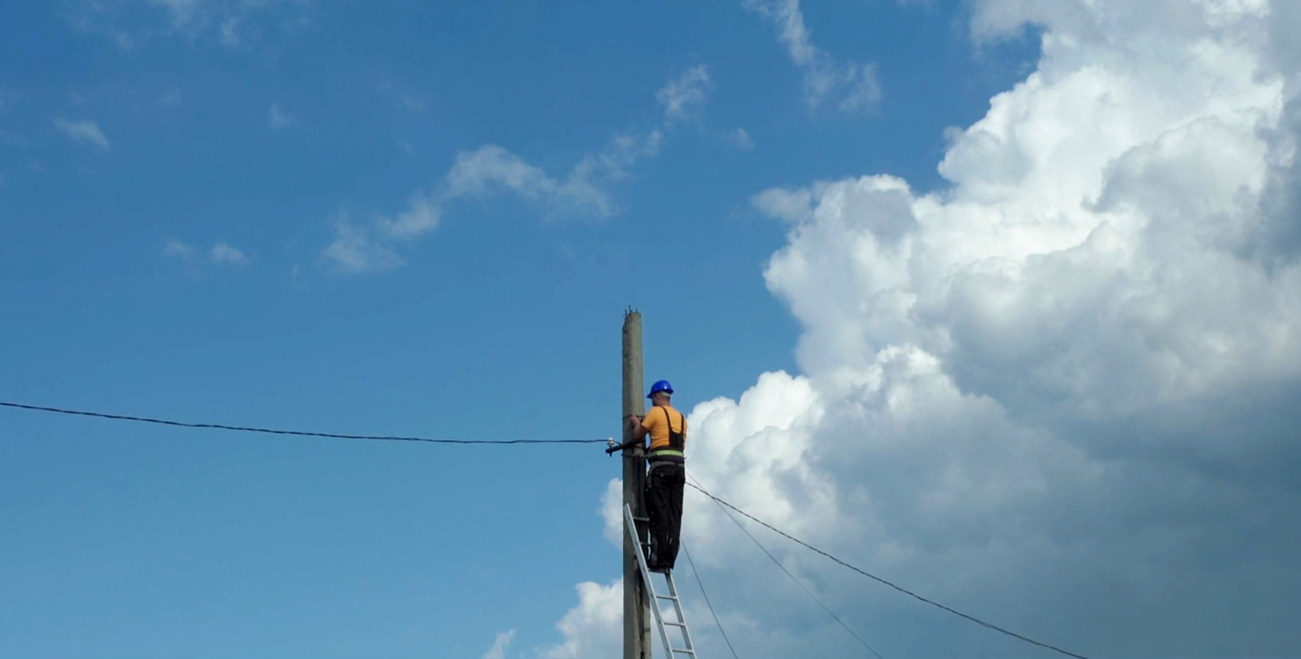 A still from Please Hold The Line. A man fixing a telephone wire.