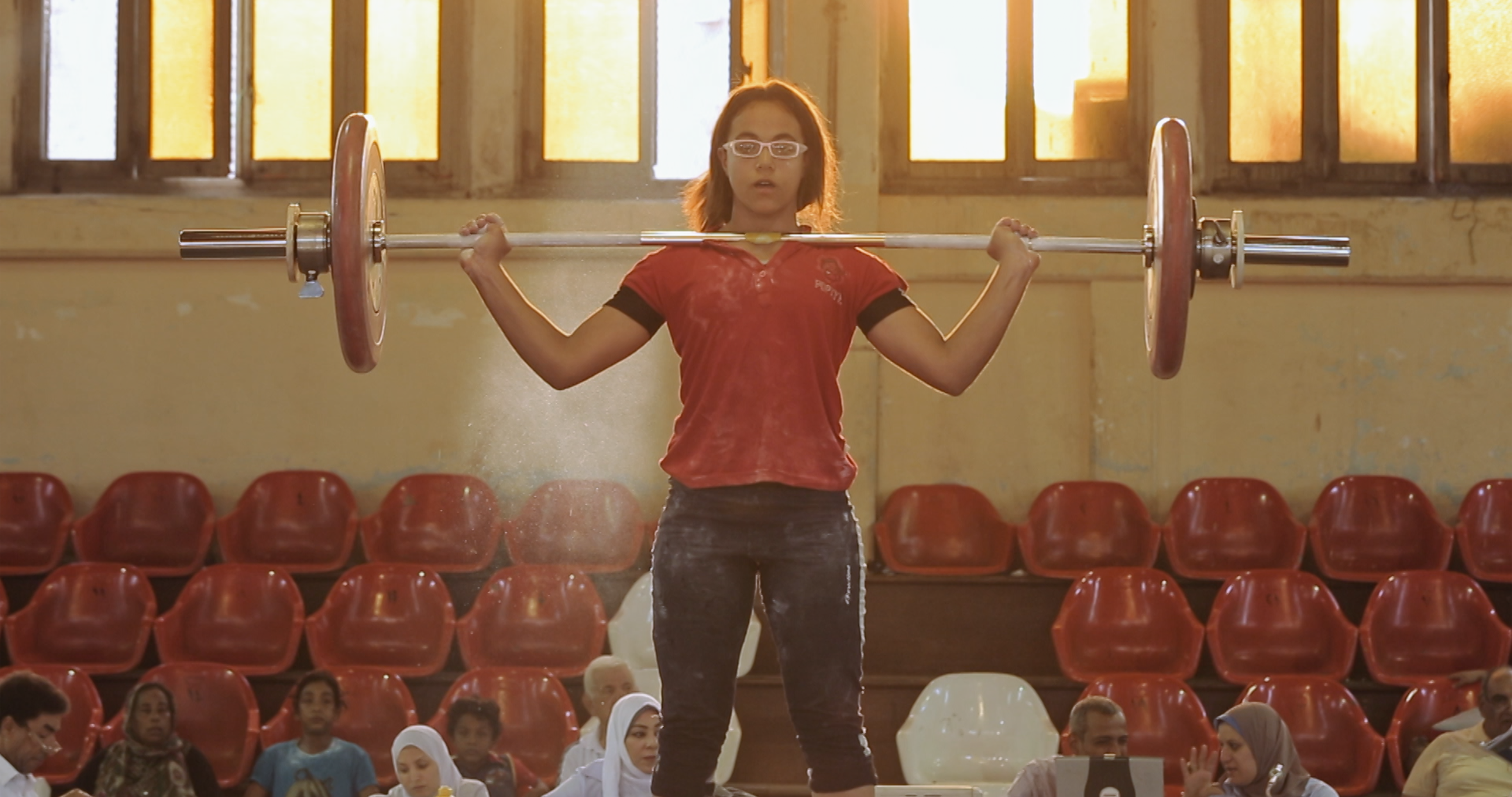 A girl in the process of weightlifting. Wearing white glasses and a red shirt, she holds the weighted bar on her chest. With red spectator seats in the background, the shot is illuminated by soft sunlight from the windows.