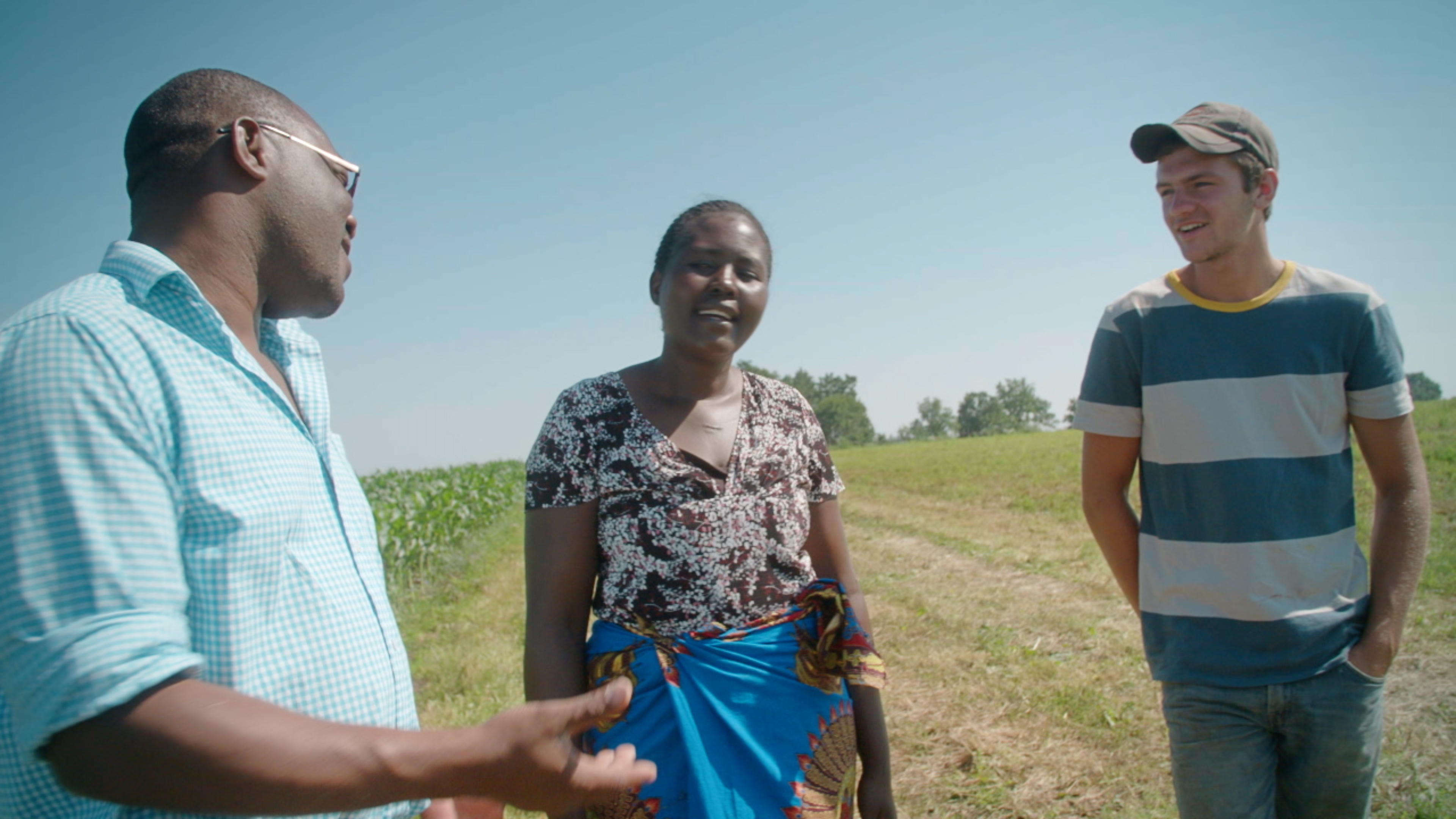 Three people stood talking in a field. A man on the left gestures with his hand towards the woman and young man stood beside him.