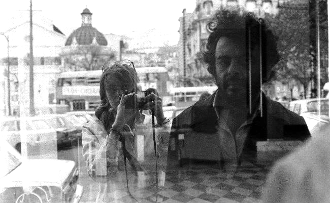 A woman and man are pictured in the reflection of a window. The woman is standing behind the man with a camera raised over her shoulder.