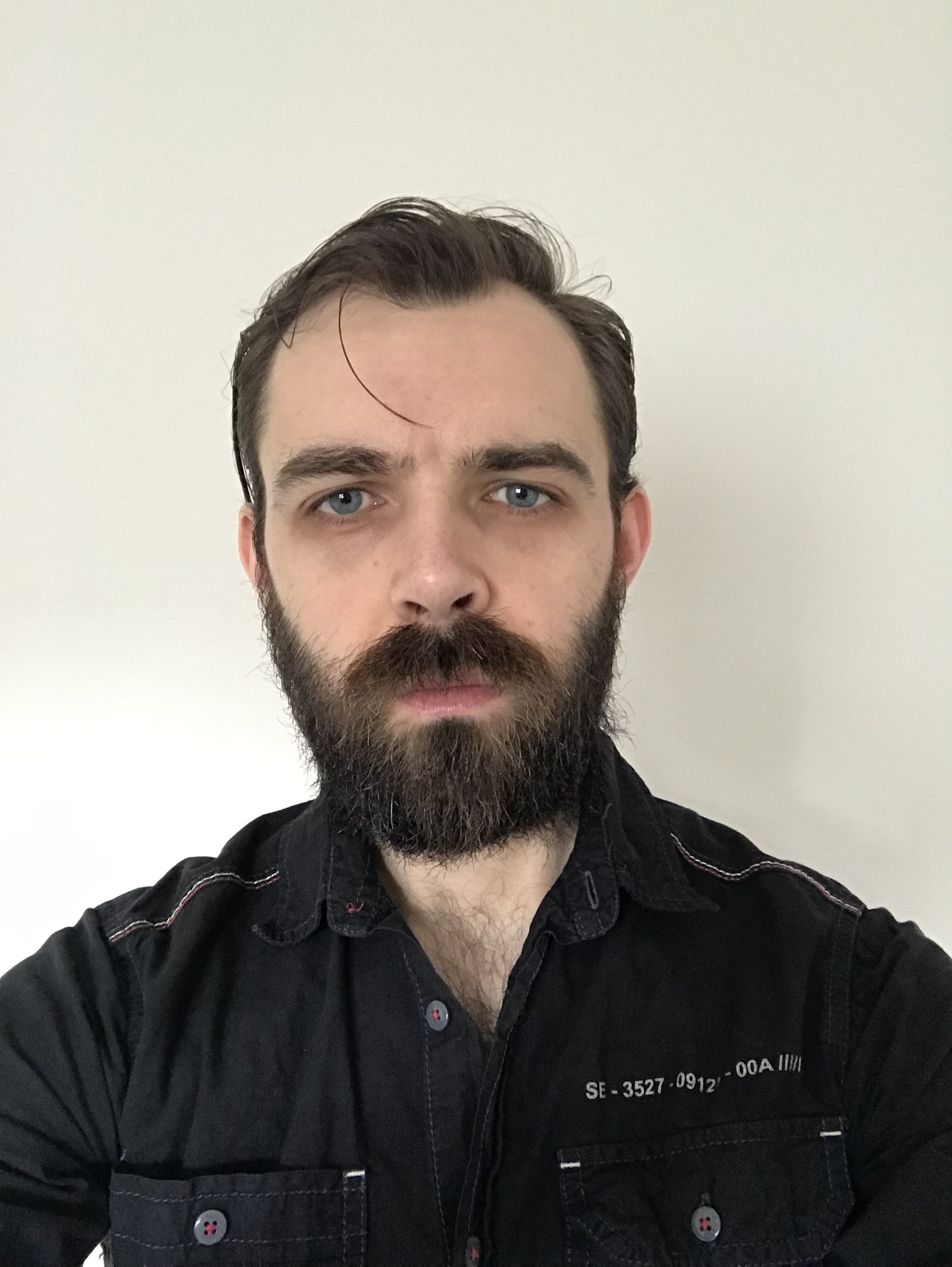 Image of a man with a dark beard and black shirt