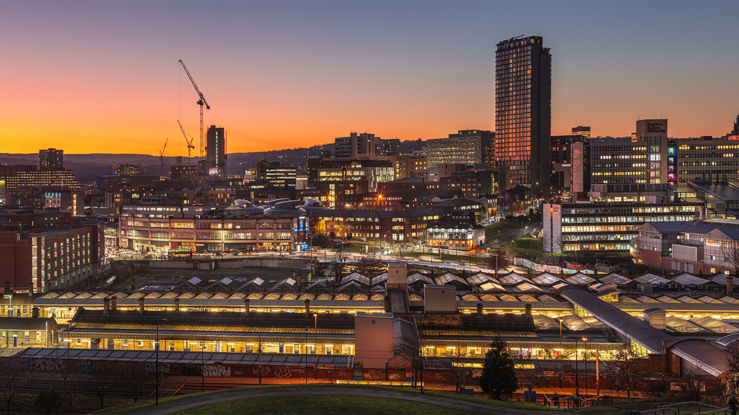 Looking over Sheffield Train Station with the city scape behind it at dusk