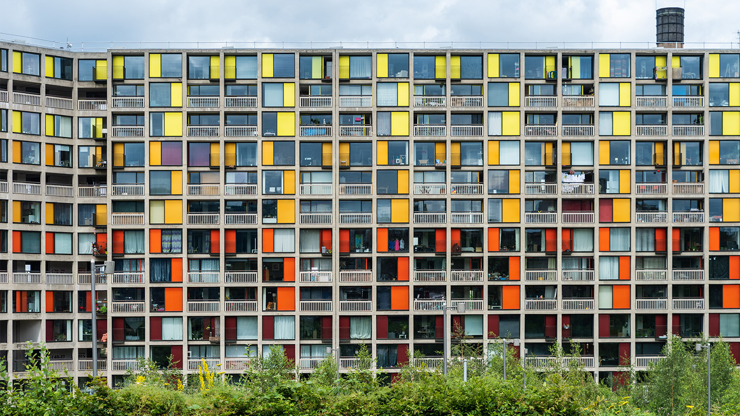 A housing block of apartments which have yellow, orange and red colouring