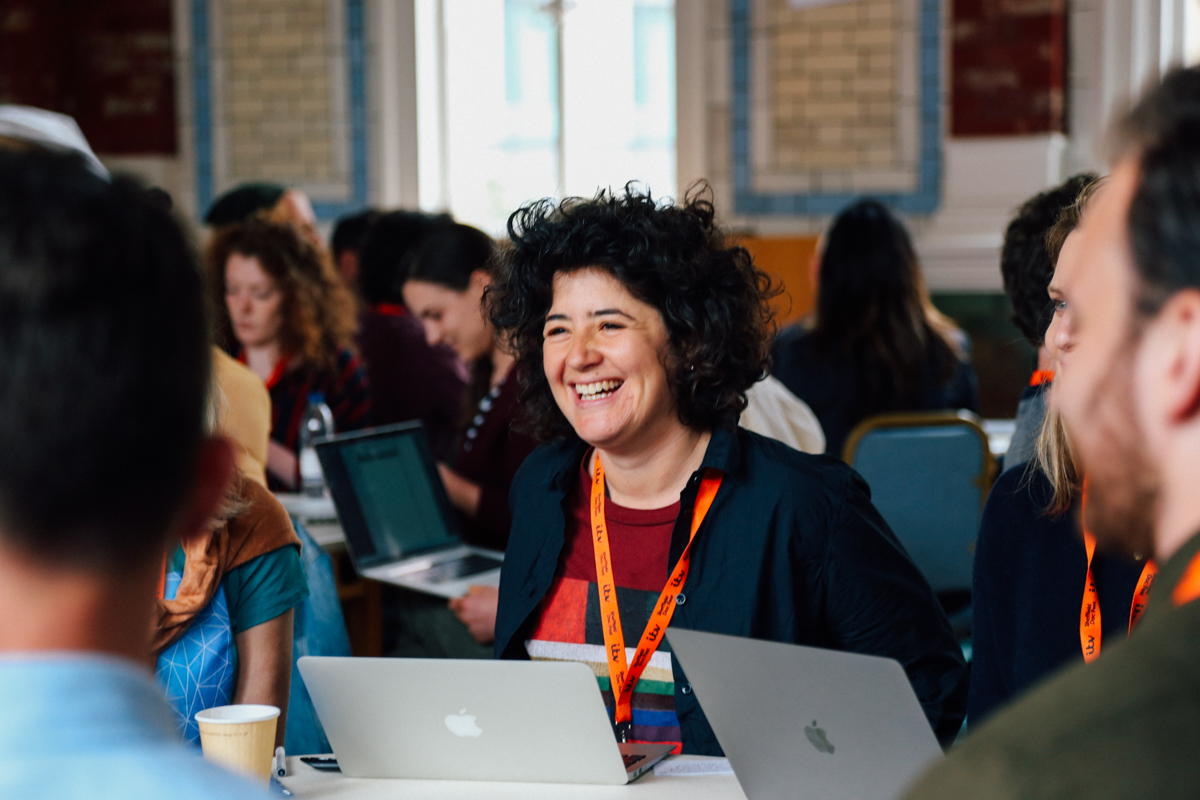 A DocFest attendee on her laptop at a table with others
