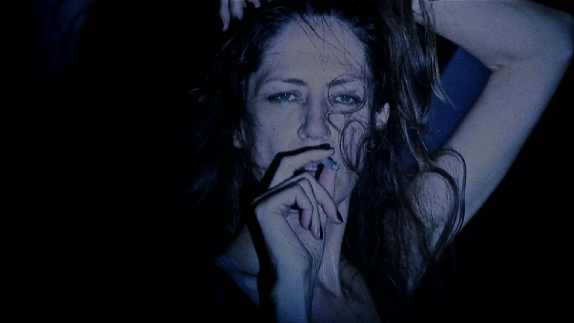 Shot of a woman smoking a cigarette. Her hair is swept across half of her face.