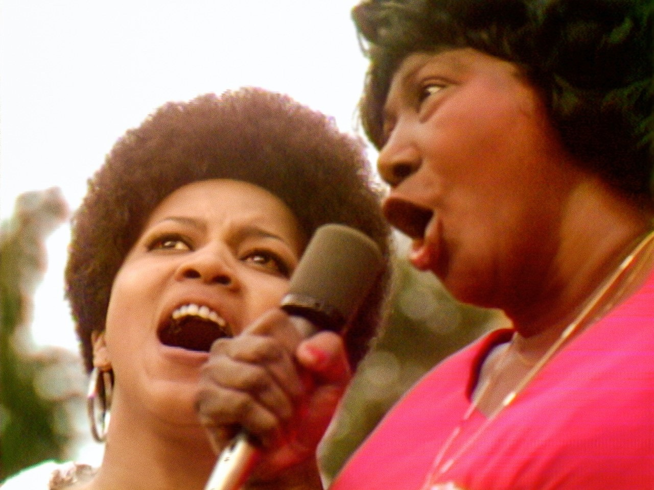 Two black women singing into a microphone
