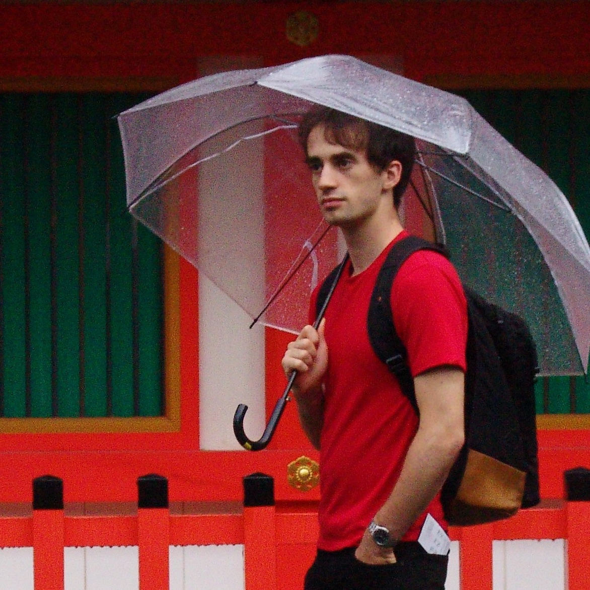Man in a red t-shirt holding an umbrella