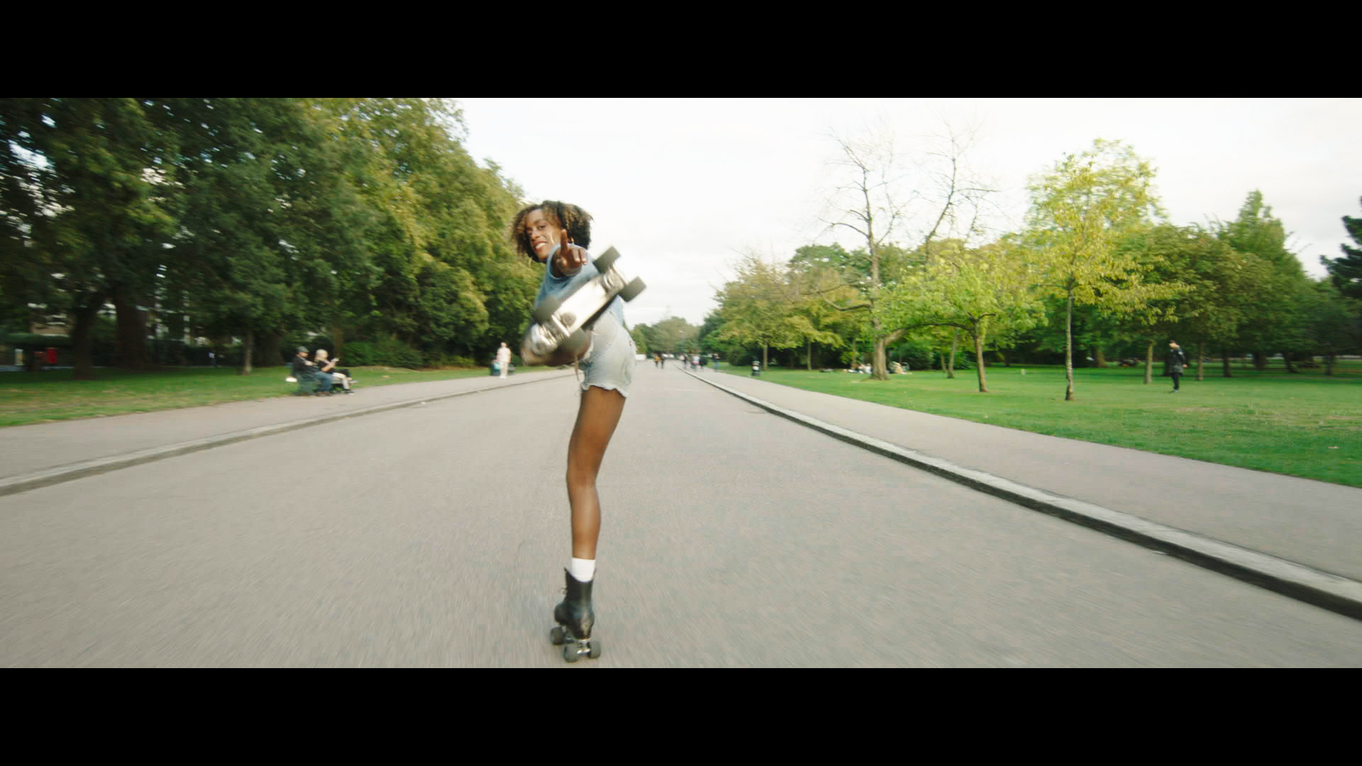 A woman rollerskates down a wide empty road. She turns her head and points with her left hand back to the camera, with her left leg outstretched behind her.