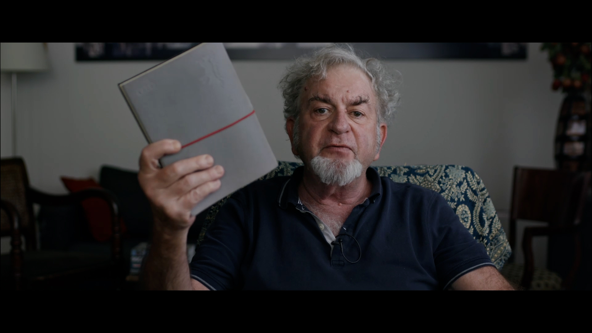 A still from The First 54 Years. A man holding a book up to the camera.