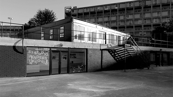 Flat roof building with large windows and doors. Window signage reads: S1 Studio Holders Takeover. Pictured in the background is a block of flats.