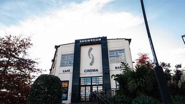 Front facade of a building pictured between shrubbery. The sign on the front of the building reads: Showroom Café Cinema Bar