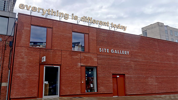 Sign reads 'everything is different today' in lights, sitting above a red brick building. White sign on the facade of the building reads'SITE GALLERY'