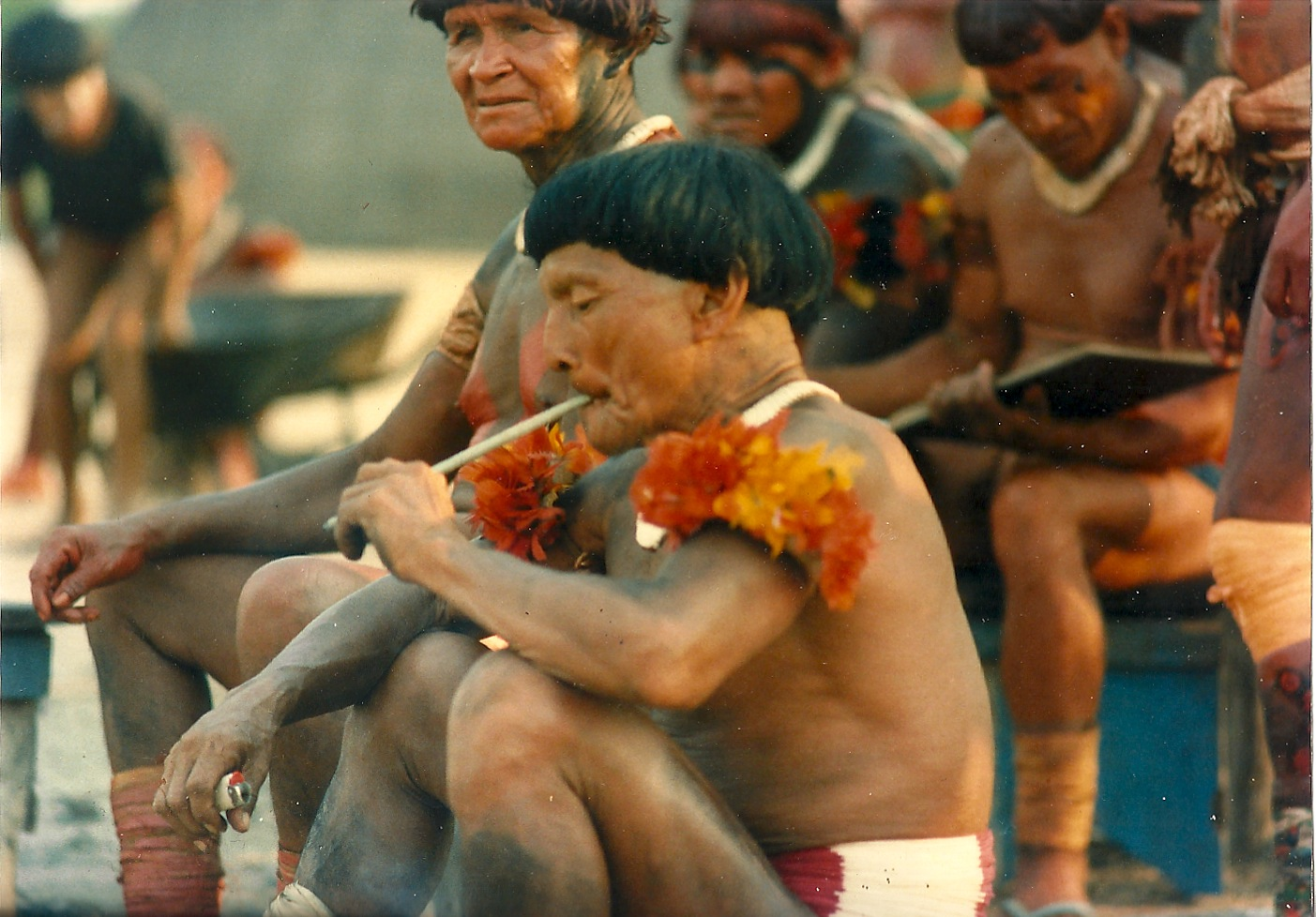 A group of indigenous people sat together. In the forefront a person is smoking a long cigarette.