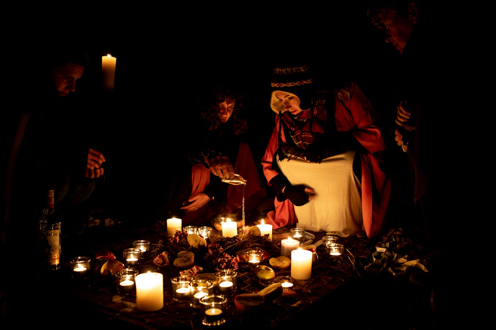 Previous Thesmophoria event. Group gathered in darkness around an assortment of candles.
