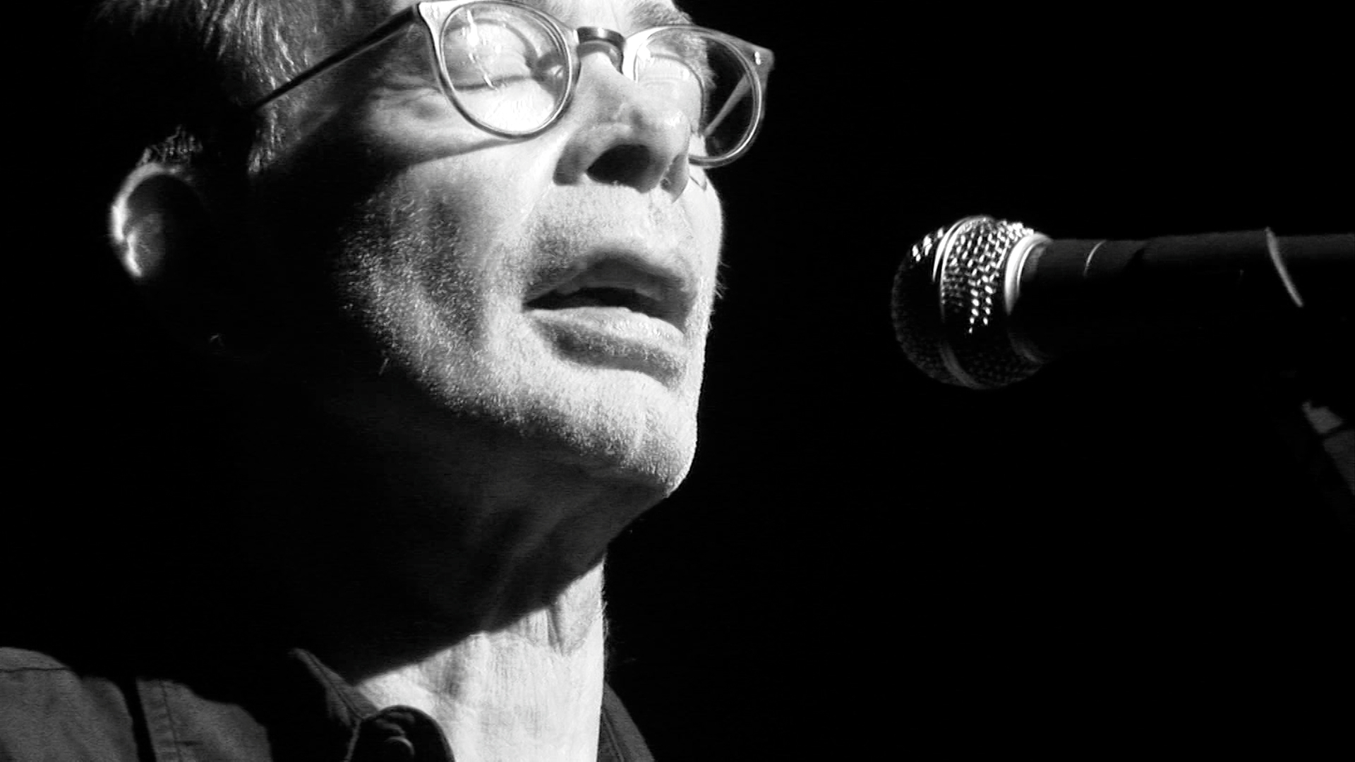 Black and white shot of a man in glasses singing into a microphone.