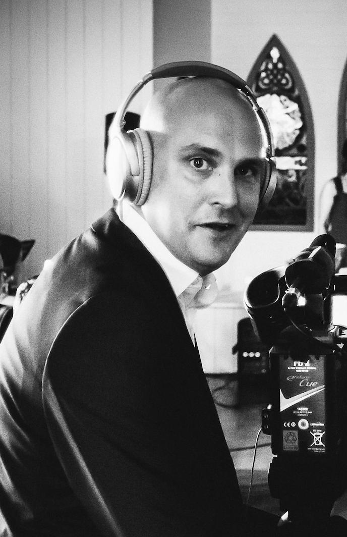 Man wearing headphones and a dark jacket