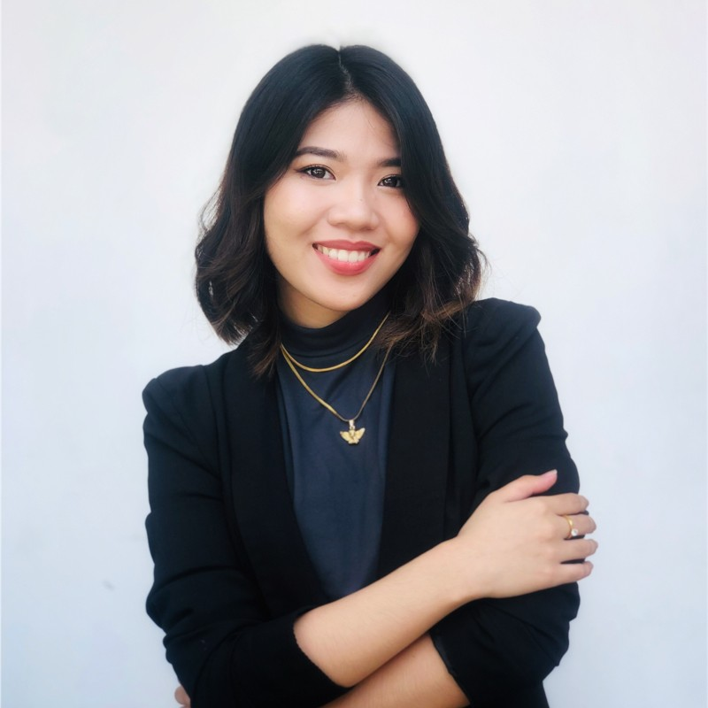 Woman standing with arms crossed wearing black blazer