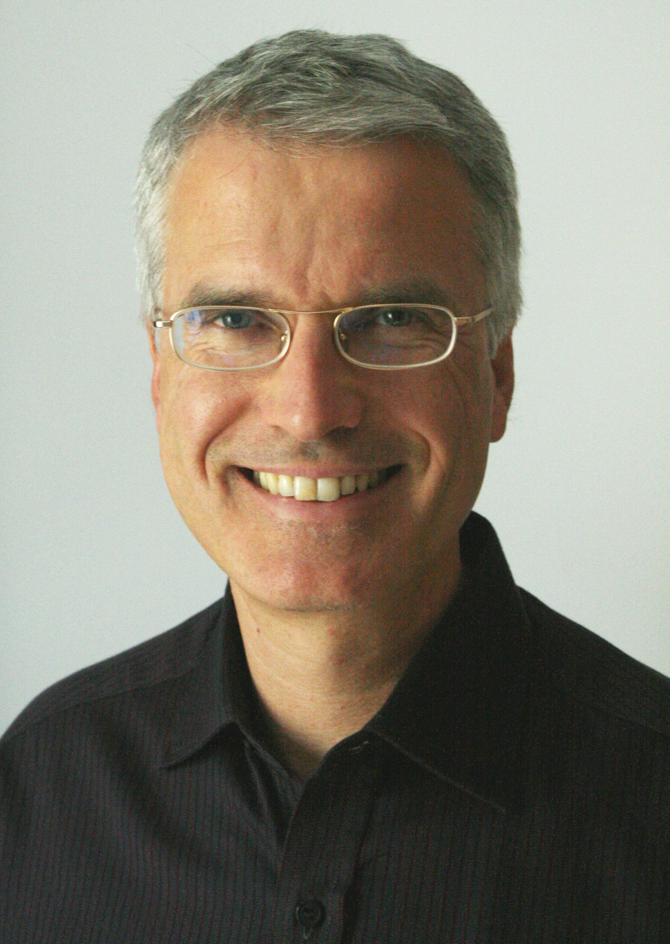 Man with grey hair and black top