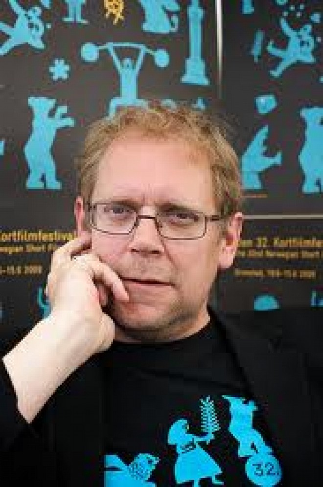 Man with ginger hair wearing a black and blue t-shirt