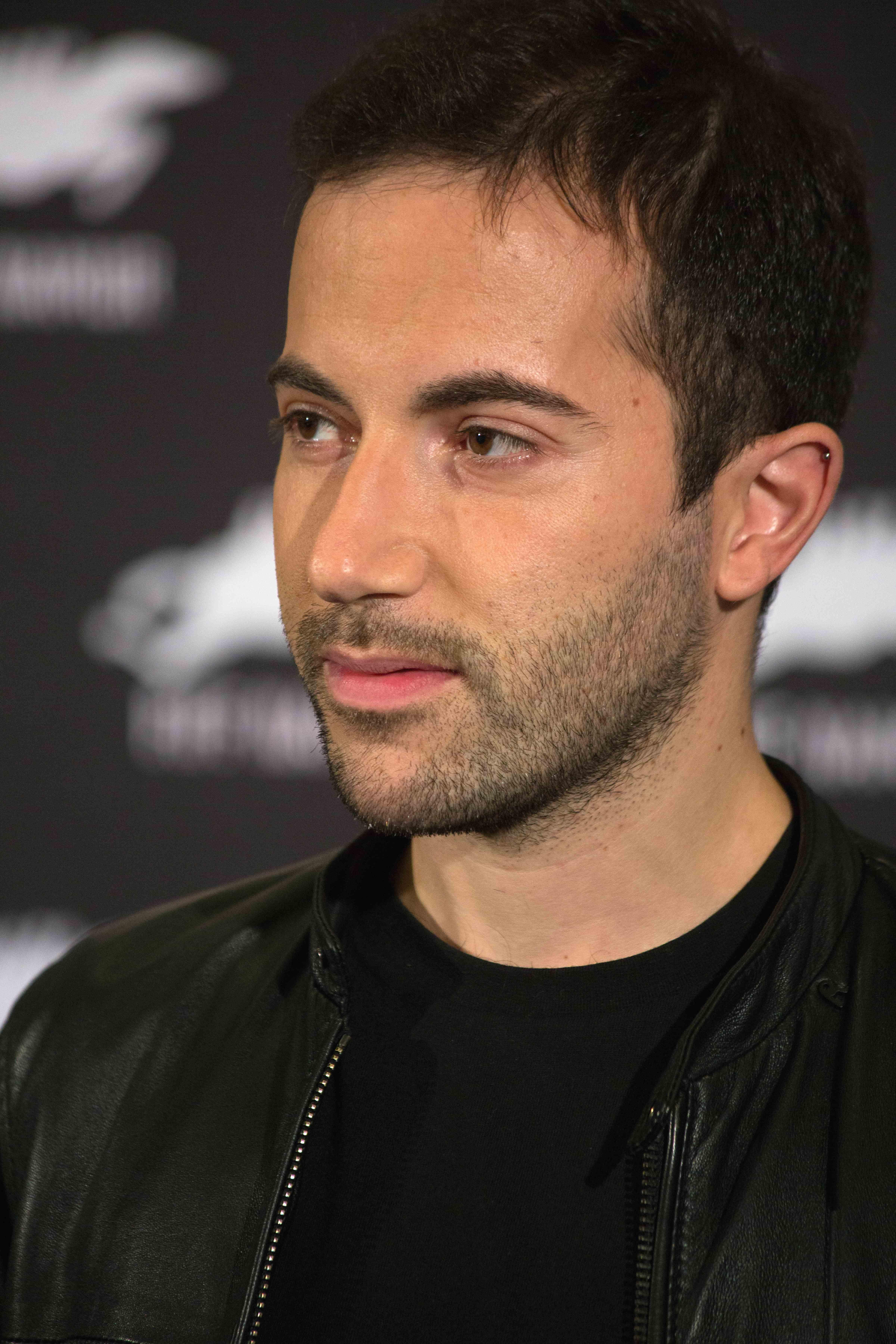 Man with dark hair and dark shirt