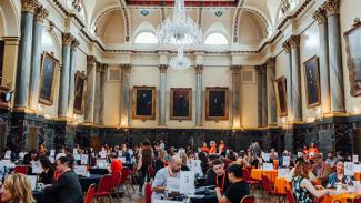 A grand hall with a large chandelier hanging centrally. Painted portraits hang along the walls in gold frames. Groups of people are pictured beneath, sat around round tables.