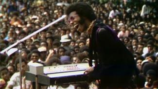 Afro-haired man in sunglasses playing the keyboard in front of a crowd of people.