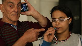 Close-up of a young girl with white glasses biting a medal. The arm of an older man points at the girl as he talks on his mobile phone.