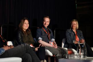 Image of 4 people smiling and sat around a table on a stage. The background is black and the people are in conversation, speaking for a panel.