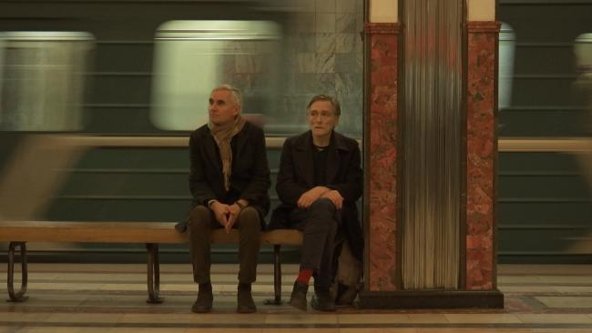 Two spies sitting on a bench in the railway station